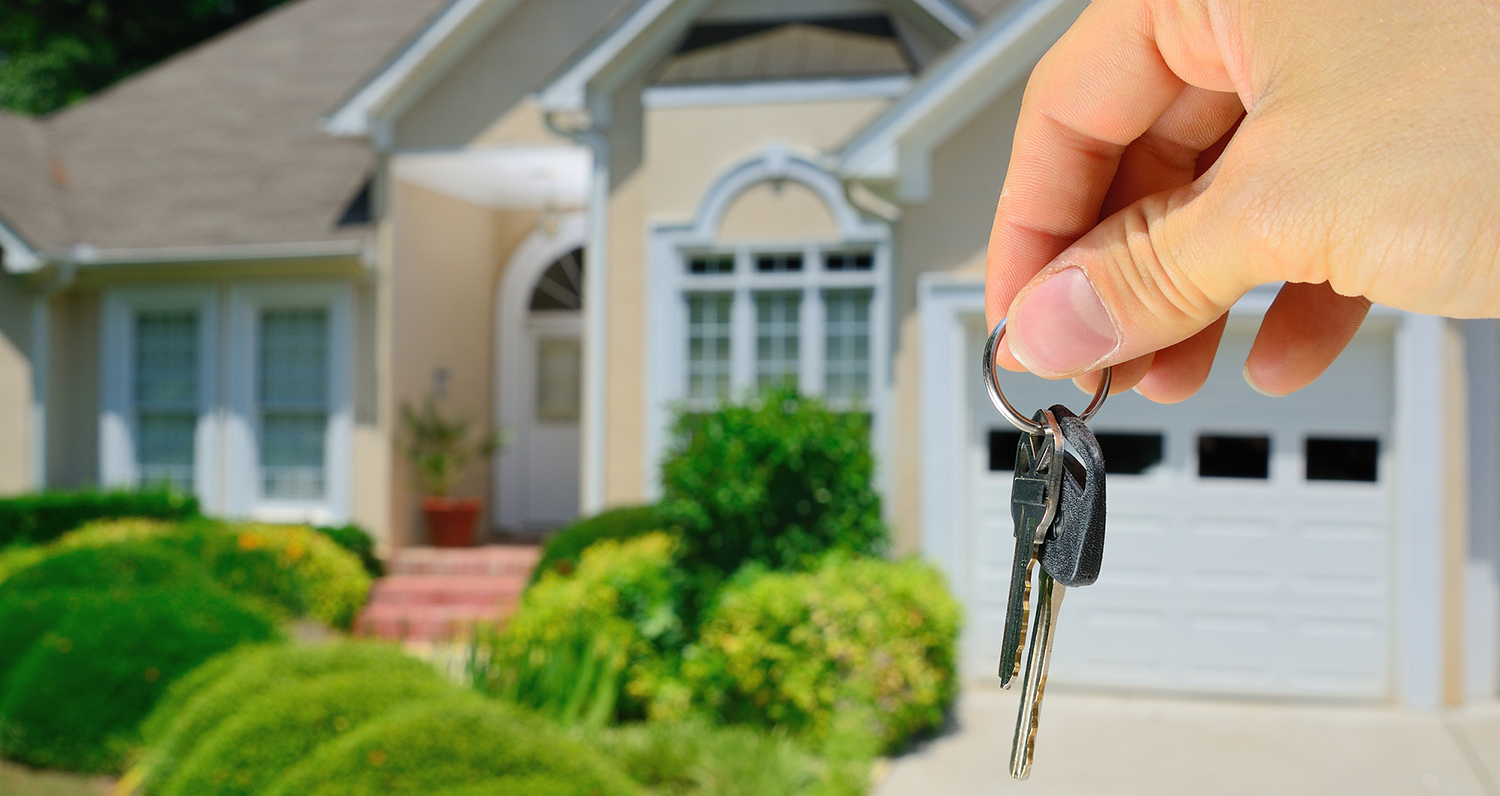 Hand holding house keys in font of a new residential property that just passed thorough home inspection services